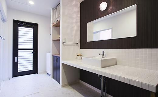 画像:白いタイルと深い色のクロスでスタイリッシュな雰囲気にした洗面室。